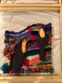 Linda A. Tapestry using linen warp, ribbon and novelty yarns and felted birds. It will be mounted on a tree slab for a more woodsy look.