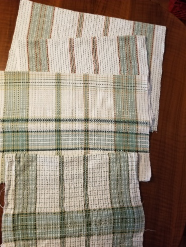 """Pat B:Warp 8/2 white and white slub from the woolery with red, light green, green, dark green, and yellow accents. The pin stripes are double threads, each in their own heddle. L-R: The towels with the red stripes were woven with the white slub. 22x30 off the loom. 18x26 after washing. The towels with the dark green stripes used to have red accents. The 3rd towel became a sampler. You are seeing the back side. Woven with a variety of slub yarns and experimented with some weft bands and accents with the 8/2. The 4th towel was woven with a double strand of fine natural white slub with a 2-bobbin shuttle. 22x33 off loom, 17 x 30 after washing. I laid in double thread pinstripes overlapping about 3"""" in the wide bands every 11 picks. A bit of a pain to do but I like the look. I put in a wide band to match the wide color band in the warp. I washed a full inch wider than the rest of the towel. Teach me not to wash the sampler before weaving the final towel."""