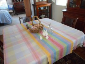 """Karen York: Spring Table Runner Fiber: 100% 8/4 cotton (Yes, carpet warp!) Structure/Sett: Plain weave, straight draw, 15 epi, 15 dent reed, 4 yard warp This is weaving kindergarten, or weaving for dummies. My desire was to weave some spring after a long, long, hard winter. I checked my ever-ready stash of carpet warp, and picked out the brightest, boldest colors I could find. I made the runner long enough to fit on both my antique tables. The kitchen table is 48"""" x 60."""" My dining room table is 48"""" x 48."""" It does what it was designed for: it certainly lights up a room. Comments: After warping my loom, I experimented with weft colors. My plan was to use a light tan, but I found that just dulled the warp down. I tried the colors in the warp, but eventually settled for a natural. That seemed to bring up the colors and not get buried in the strong colors of the warp. I wove a 2"""" hem of 8/2 unmercerized cotton in natural, then 72"""" of the 8/4 unmercerized cotton in natural, then finished with the 8/2. When hand hemmed, the runner measured 72"""" x 19. After wet finishing, it measured 60% x 17."""""""