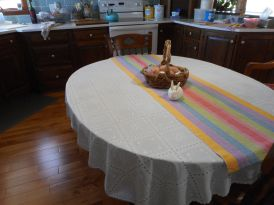 """Karen Y Spring Table Runner Fiber: 100% 8/4 cotton (Yes, carpet warp!) Structure/Sett: Plain weave, straight draw, 15 epi, 15 dent reed, 4 yard warp This is weaving kindergarten, or weaving for dummies. My desire was to weave some spring after a long, long, hard winter. I checked my ever-ready stash of carpet warp, and picked out the brightest, boldest colors I could find. I made the runner long enough to fit on both my antique tables. The kitchen table is 48"""" x 60."""" My dining room table is 48"""" x 48."""" It does what it was designed for: it certainly lights up a room. Comments: After warping my loom, I experimented with weft colors. My plan was to use a light tan, but I found that just dulled the warp down. I tried the colors in the warp, but eventually settled for a natural. That seemed to bring up the colors and not get buried in the strong colors of the warp. I wove a 2"""" hem of 8/2 unmercerized cotton in natural, then 72"""" of the 8/4 unmercerized cotton in natural, then finished with the 8/2. When hand hemmed, the runner measured 72"""" x 19. After wet finishing, it measured 60% x 17."""""""